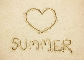 Word summer and heart shape on sand