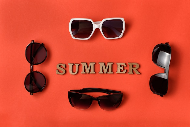Word summer from wooden letters. four sun glasses on live coral background. travel concept