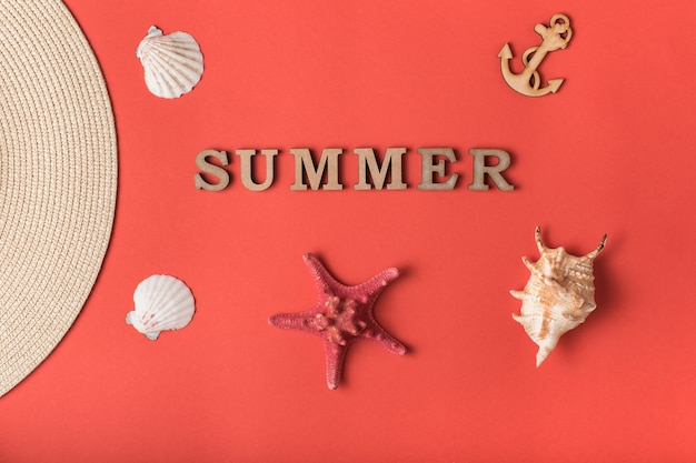 Word summer from wooden letters. seashells, anchor and part of a hat. live coral background.