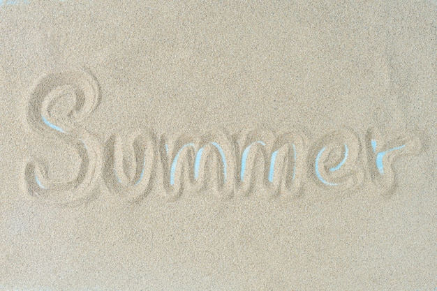 The word summer is writting on the sand. summer background.