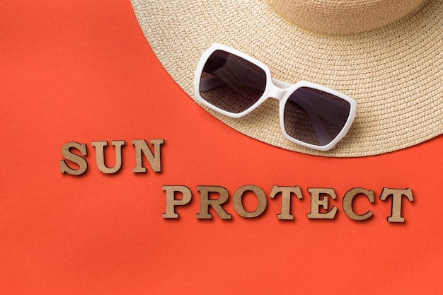 Word sun protect from wooden letters. sun glasses and a hat. ba travel concept