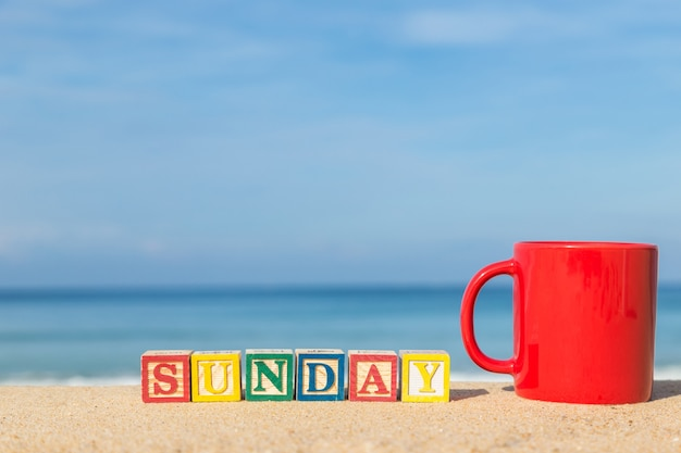 Word sunday in colorful alphabet blocks and coffee cup on tropical beach, phuket thailand
