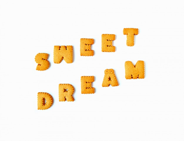 The word sweet dream spelled with alphabet biscuits isolated on white background