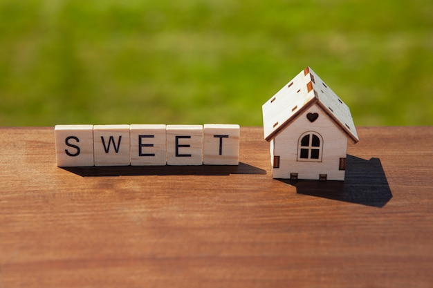 Word sweet of wooden letters and small toy wooden house on brown surface