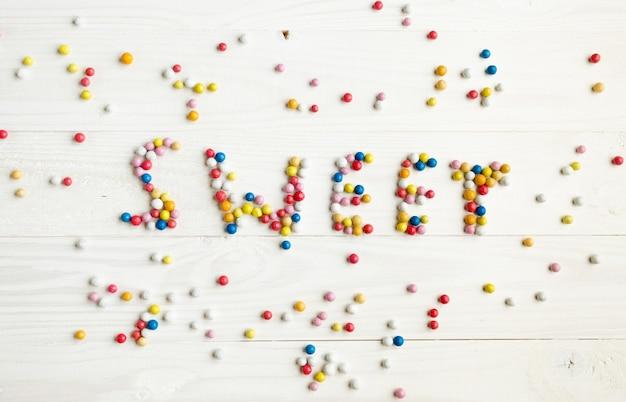白地に小さなカラフルなキャンディーで書かれた言葉の甘い