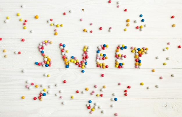 Word sweet written by little colorful candies on white