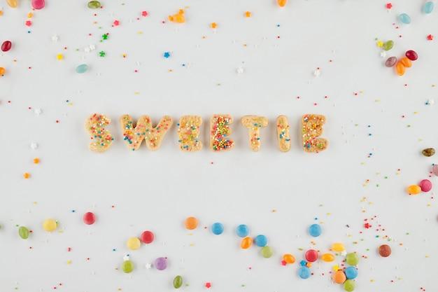수제 설탕 쿠키와 뿌리와 사탕으로 만든 단어 스위티