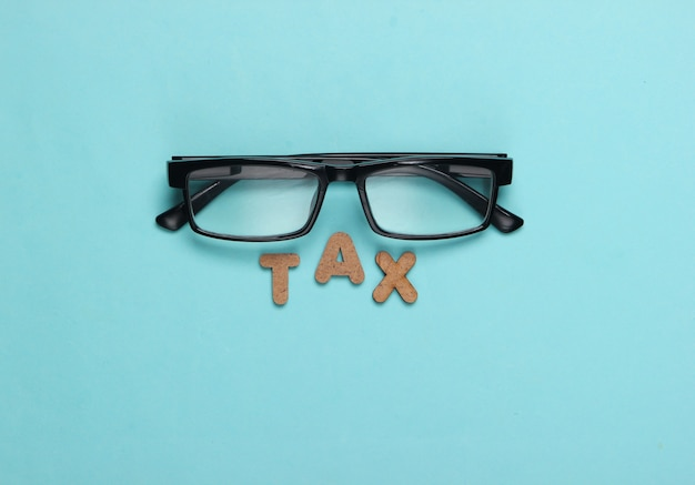Word tax and glasses on blue