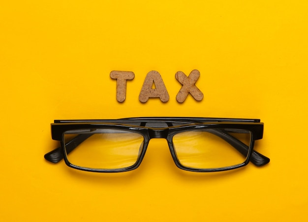 Word tax and glasses on yellow
