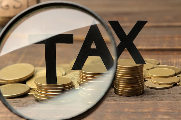 The word tax under a magnifying glass and a stack of coins on a brown wooden background.