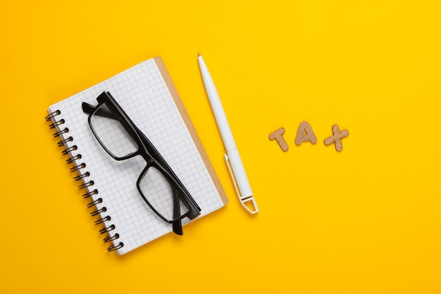 Word tax and notebook with glasses on yellow