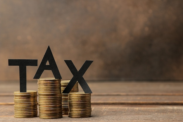 The word tax and a stack of coins on a brown wooden background. with space for text