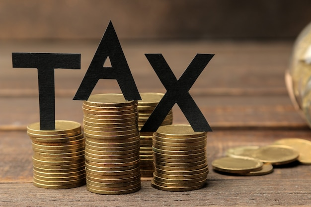 The word tax and a stack of coins on a brown wooden background.