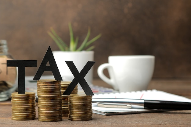 The word tax and a stack of coins with a notebook pen and coffee on a brown wooden background.