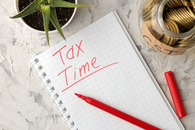The word tax time in a notebook with a jar of coins and a flower on a light concrete background. view from above