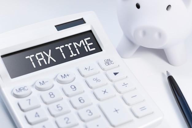 Слово налоговое время на калькуляторе. бизнес и налоговая концепция на белом фоне. вид сверху.