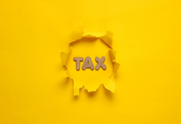 The word tax in a torn hole of yellow surface.