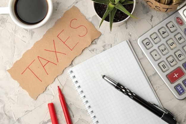 The word taxes on a sheet of paper in a notebook with coffee and pen on a light concrete background. view from above