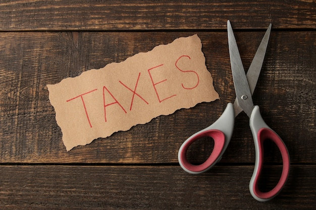 The word taxes with scissors on a brown wooden background. view from above