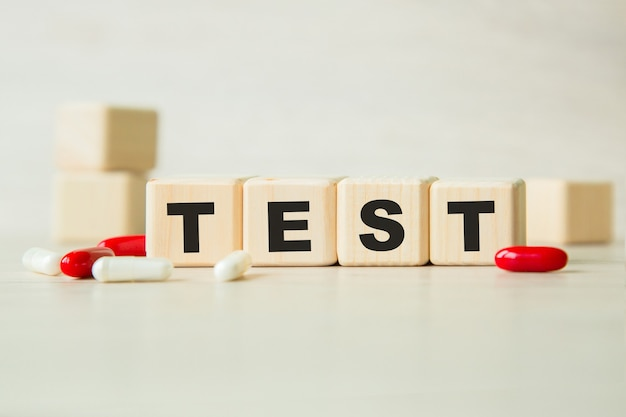 The word test is written on a wooden cubes structure with tablets