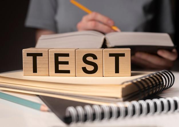 Слово тест на деревянные кубики и студент, готовящийся к нему