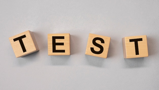 Слово тест на деревянных кубиках на сером фоне