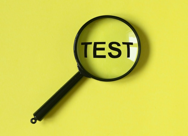 Word test on yellow background through magnifying lens