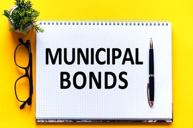 Текст слова муниципальные облигации на белой карточке, черными буквами. ручка, очки и зеленый цветок на желтой стене. концепция бизнеса и образования.