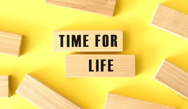 The word time for life is written on a wooden blocks on a yellow background