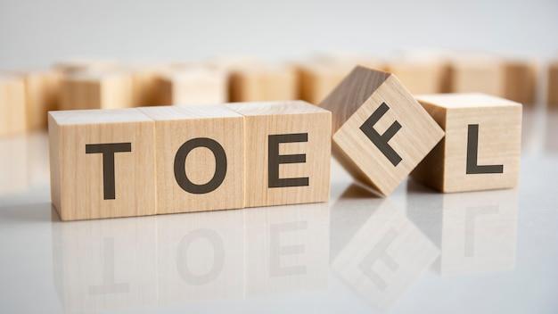 나무 큐브, 회색 배경에 단어 toefl입니다. 테이블의 거울 표면에 반사. 외국어로서의 영어 시험