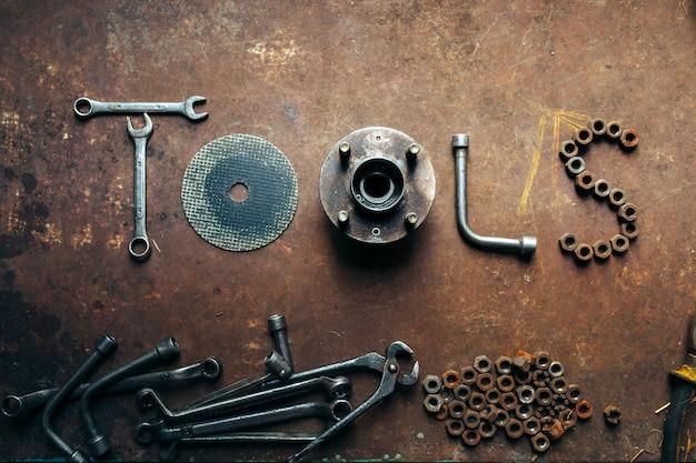 녹슨 금속 책상에 렌치 너트와 볼트로 만든 단어 도구