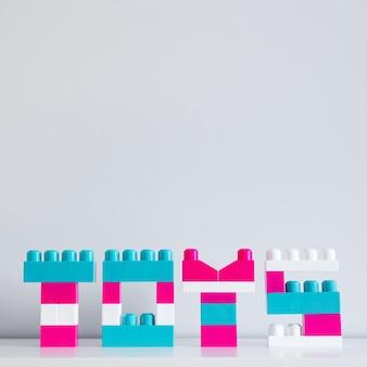 おもちゃコンストラクターと壁の背景の上のコピースペースの折り畳まれた単語のおもちゃ