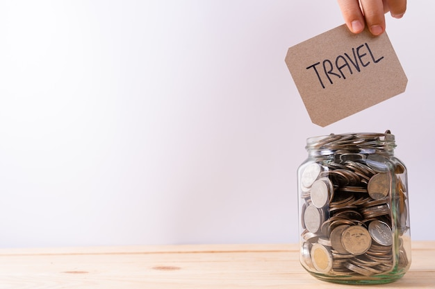 Word travel written on piece of cardboard next to glass jar with coins on wooden table