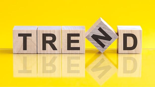 Слово тренд состоит из деревянных строительных блоков, лежащих на столе и на светло-желтом фоне.