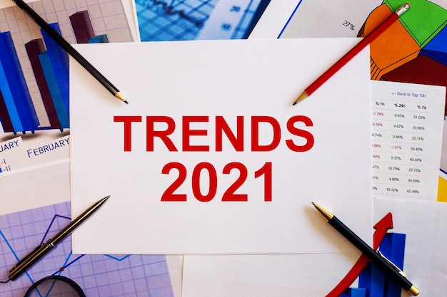 The word trends 2021 is written on a white background near colored graphs, pens and pencils. business concept