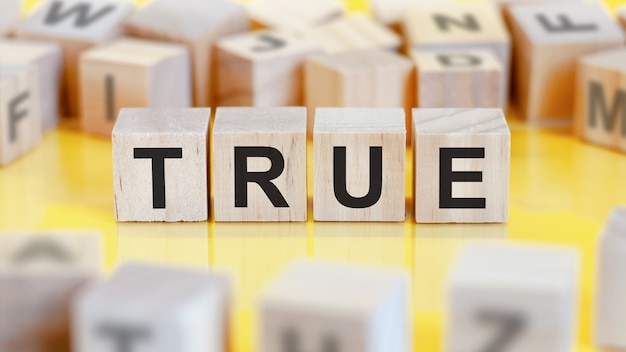 The word true is written on a wooden cubes structurefinancial concept.