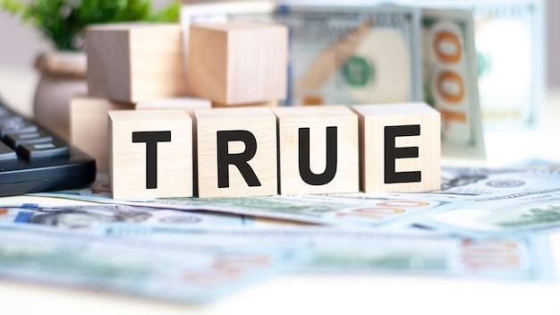 The word true on wood cubes, banknotes and calculator on the surface
