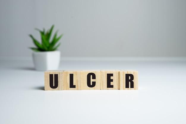 Слово язва из деревянных блоков на деревянных и сером фоне, здравоохранение и медицинская концепция.