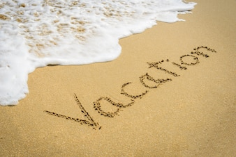 Word vacation on the beach sand - vacation and travel