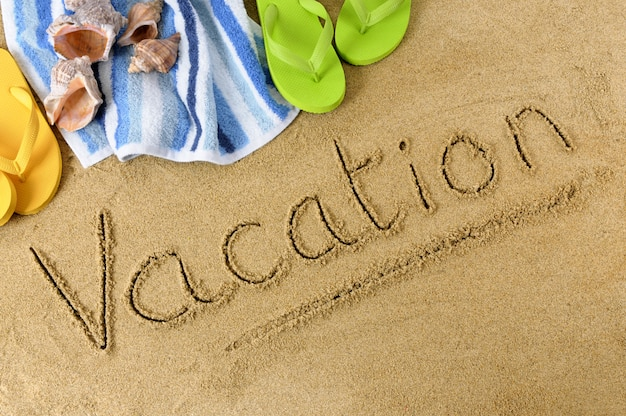 The word vacation written in sand with flip flops and beach towel