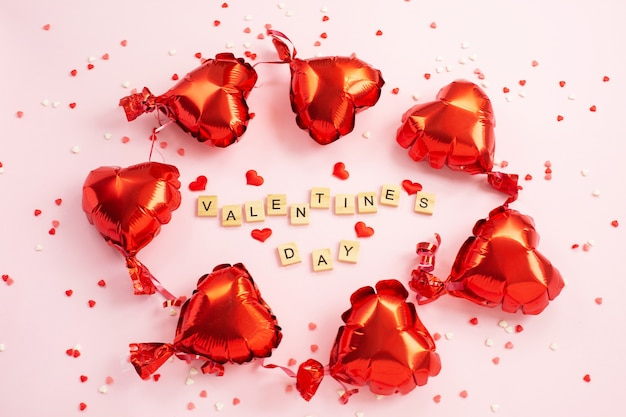 The word valentine s day from letter blocks and red hearts foil balloons around.