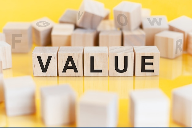 The word value is written on a wooden cubes structure. blocks on a bright yellow background. can be used for business, education, financial concept. selective focus.