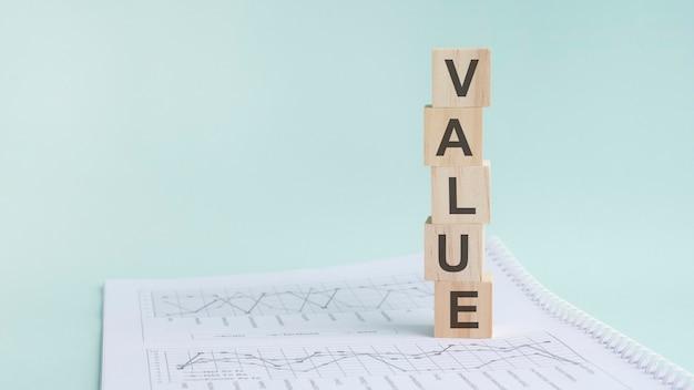 木製のビルディングブロック、薄緑色の背景を持つ単語の値。背景、ビジネスコンセプトに数字が記載されたドキュメント。左側のテキスト用のスペース。正面図