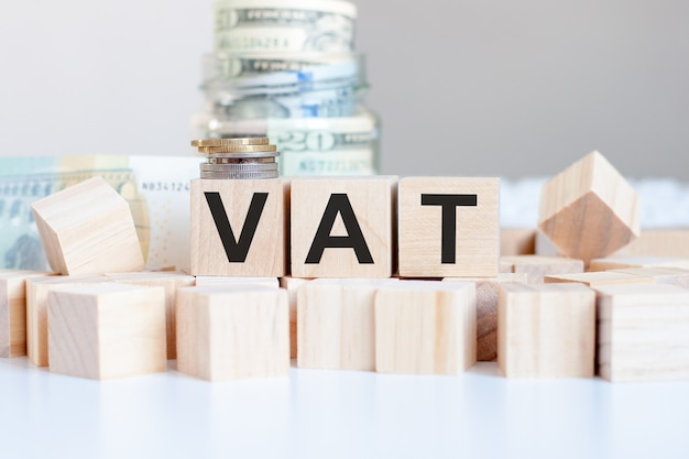 The word vat on the wooden blocks and a bank with money in the wall, business concept