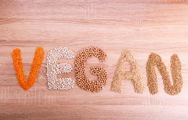 Word vegan made of lentils, buckwheat, beans, rice and chickpeas.