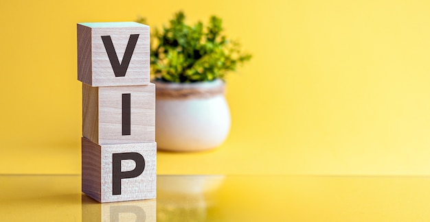 Word vip made with wood building blocks on a light yellow background