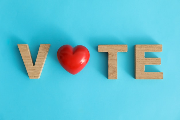 Word vote made of wooden letters and heart on blue surface