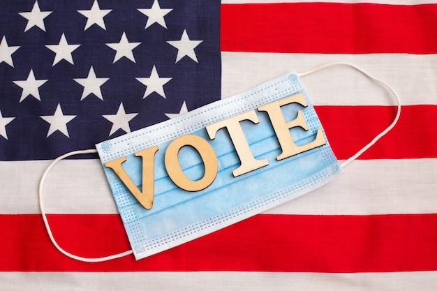 Голосование слова на медицинской защитной маске против вируса на фоне американского флага. выборное голосование. выборы в сша.