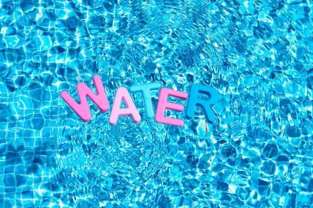 Слово вода в цветах, плавающая над пространством для копии бассейна