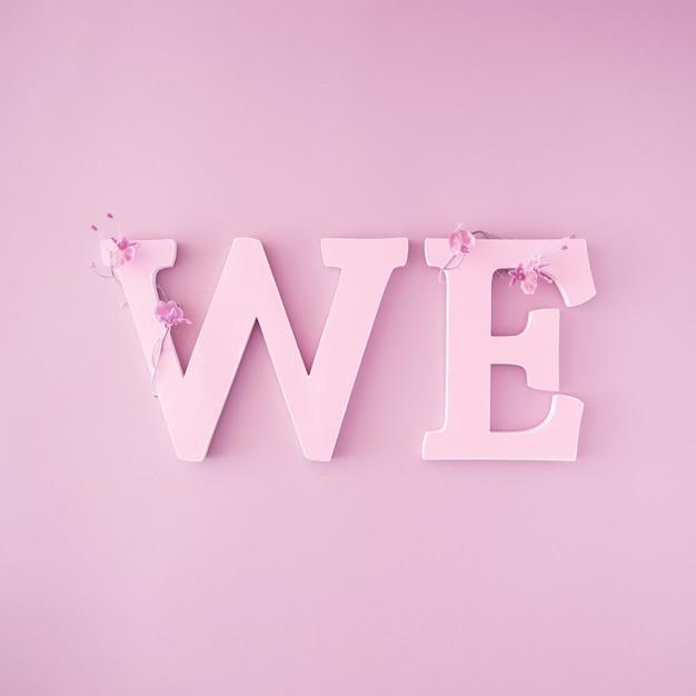 モノクロピンク色の単語we。最小限のバレンタインのフラットレイ構成。